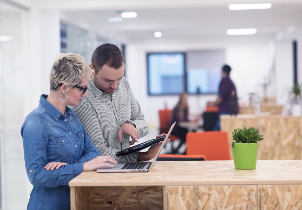Business team members using laptop and tablet in office